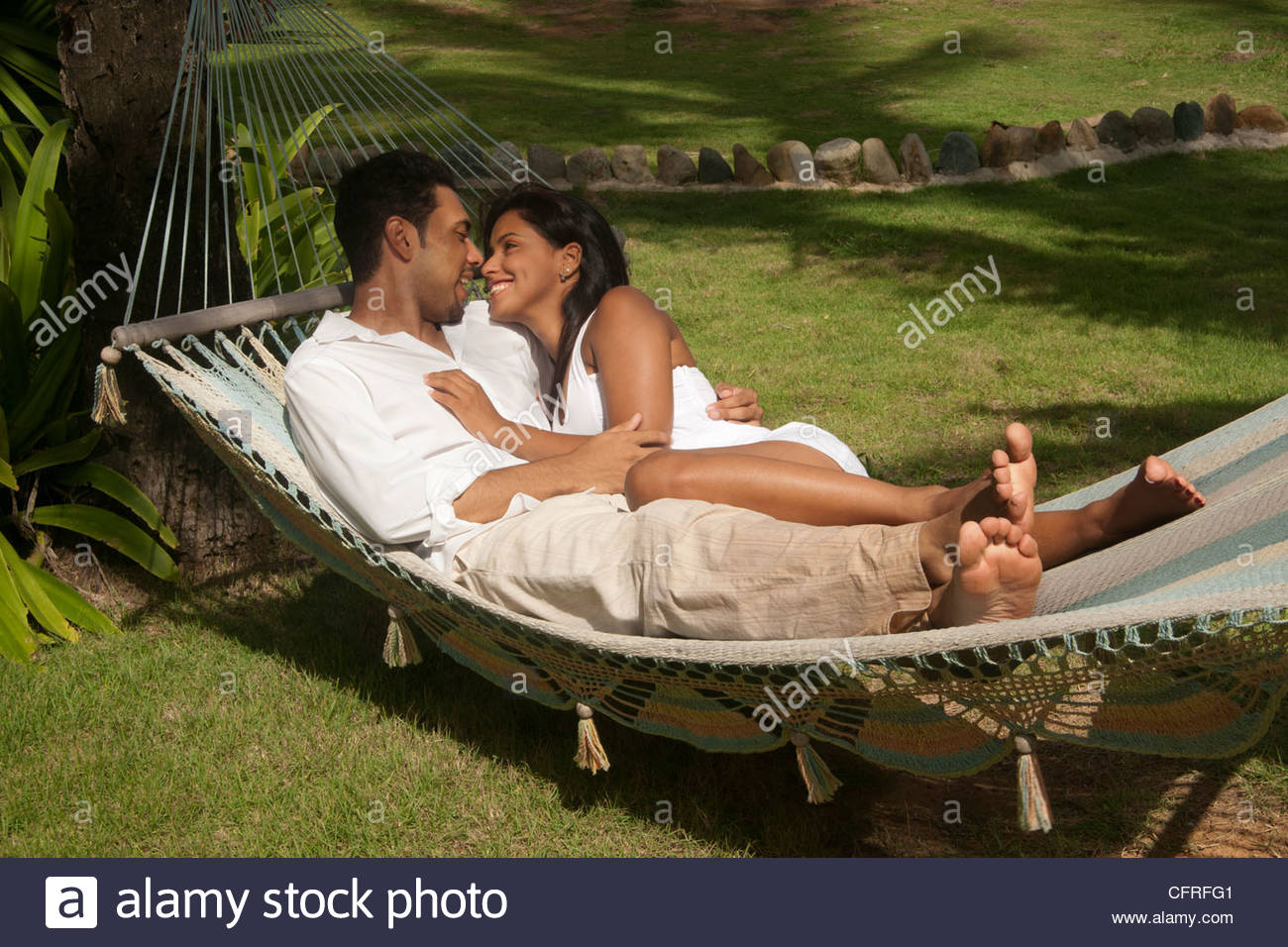 Hispanic couple relaxing in a hammock, Luquillo, Puerto Rico, United States of America, Central America - Stock Image