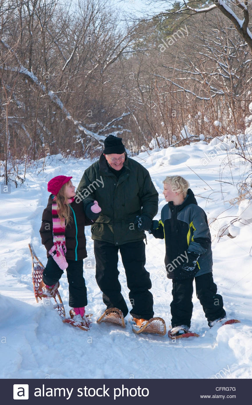 Grandfather and two grandchildren snowshoeing in a snowy forest, Rochester, Minnesota, United States of America, - Stock Image