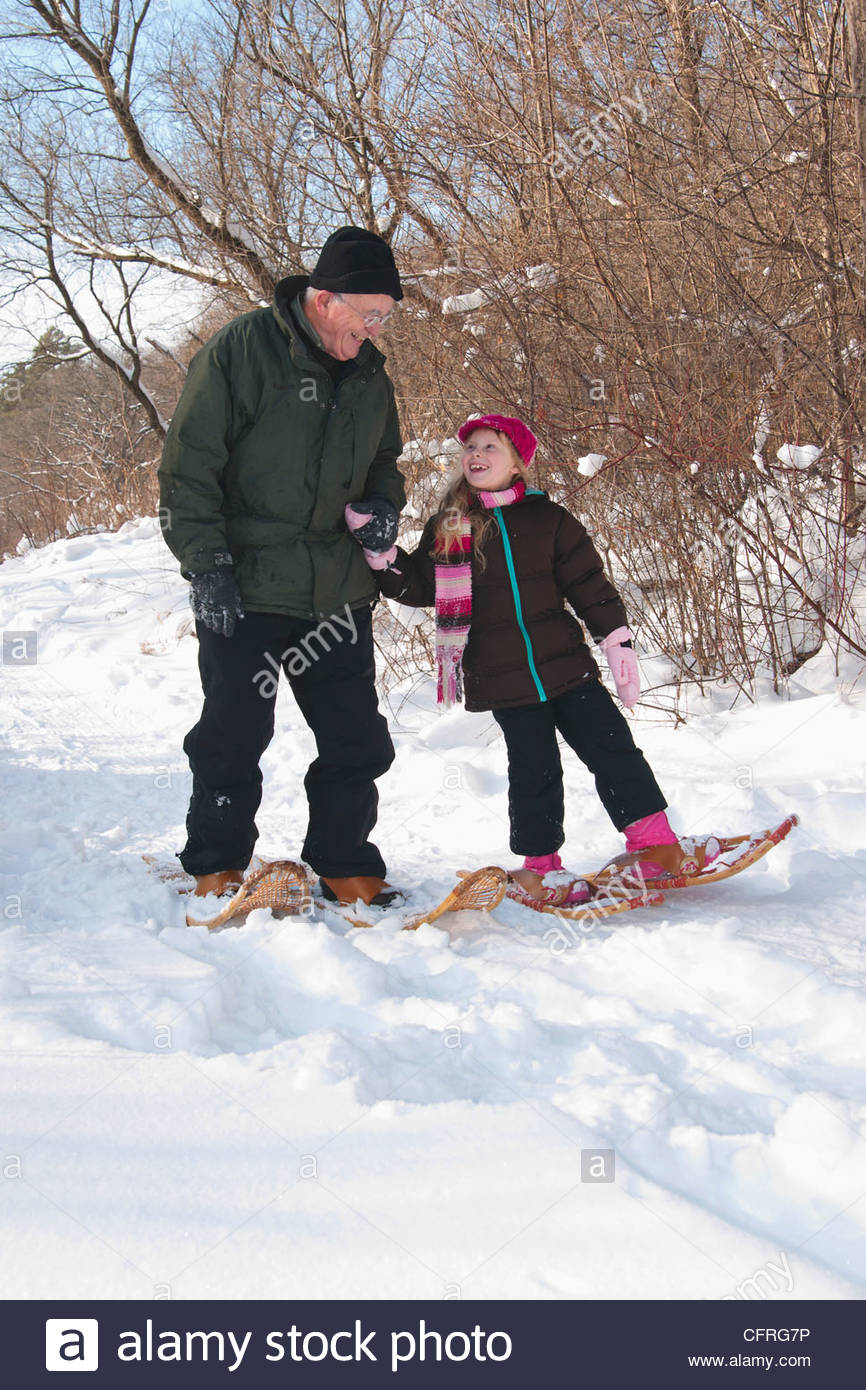 Grandfather and granddaughter snowshoeing in a snowy forest, Minnesota, United States of America, North America - Stock Image