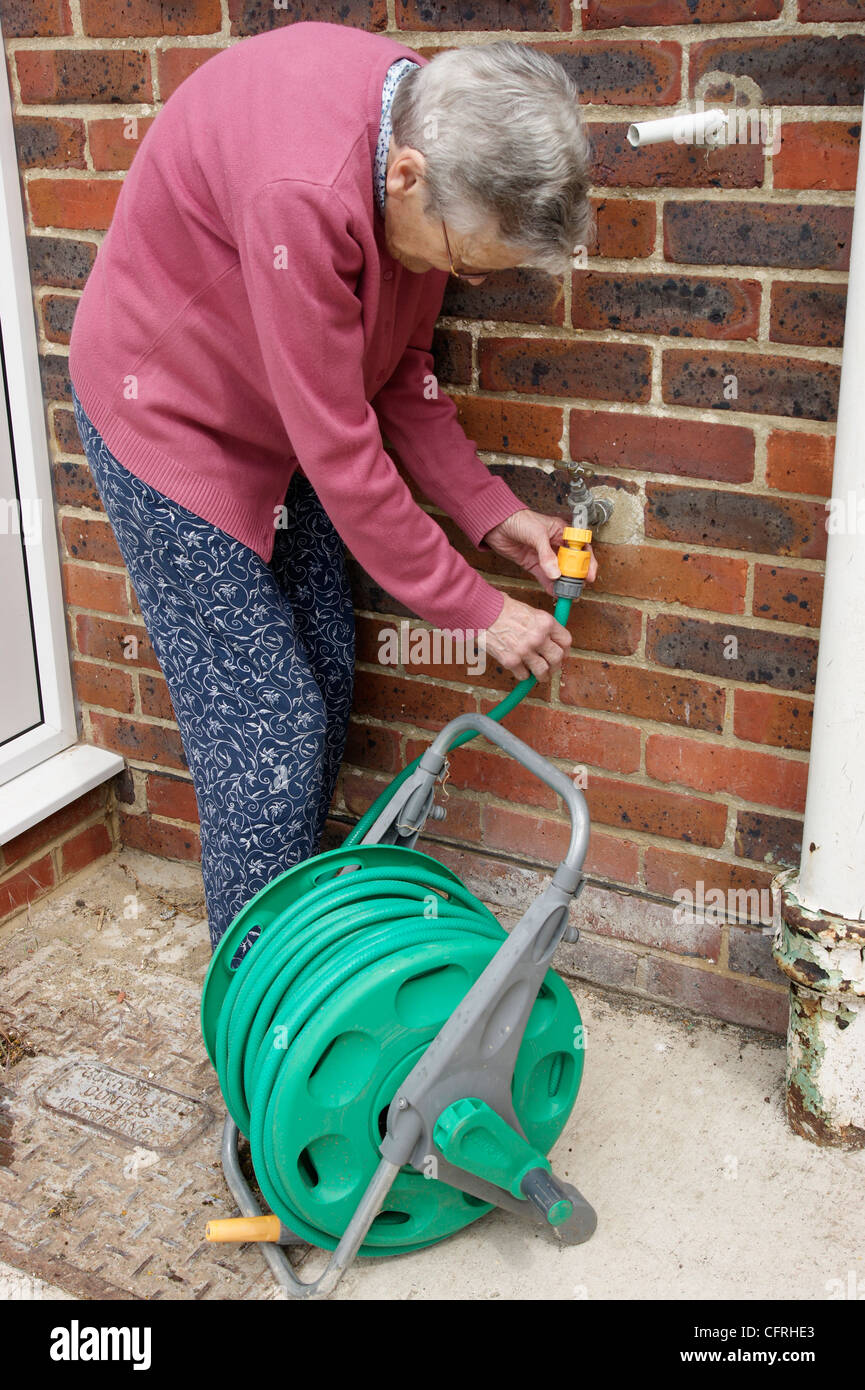 Elderly woman attaching hose to a garden tap - Stock Image