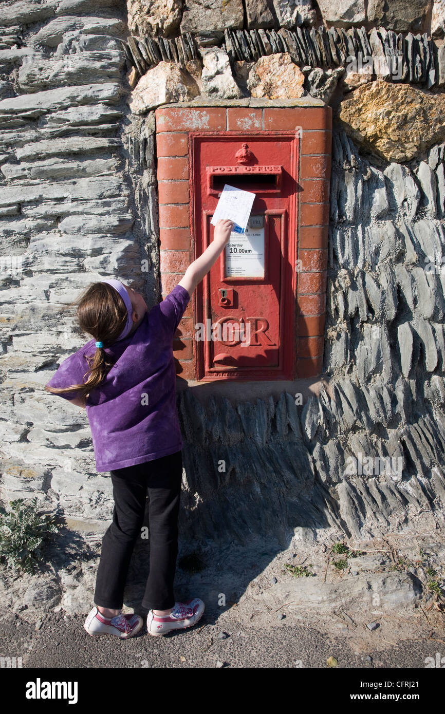Little girl posting postcards into a red postbox in Woolacombe, Devon - Stock Image