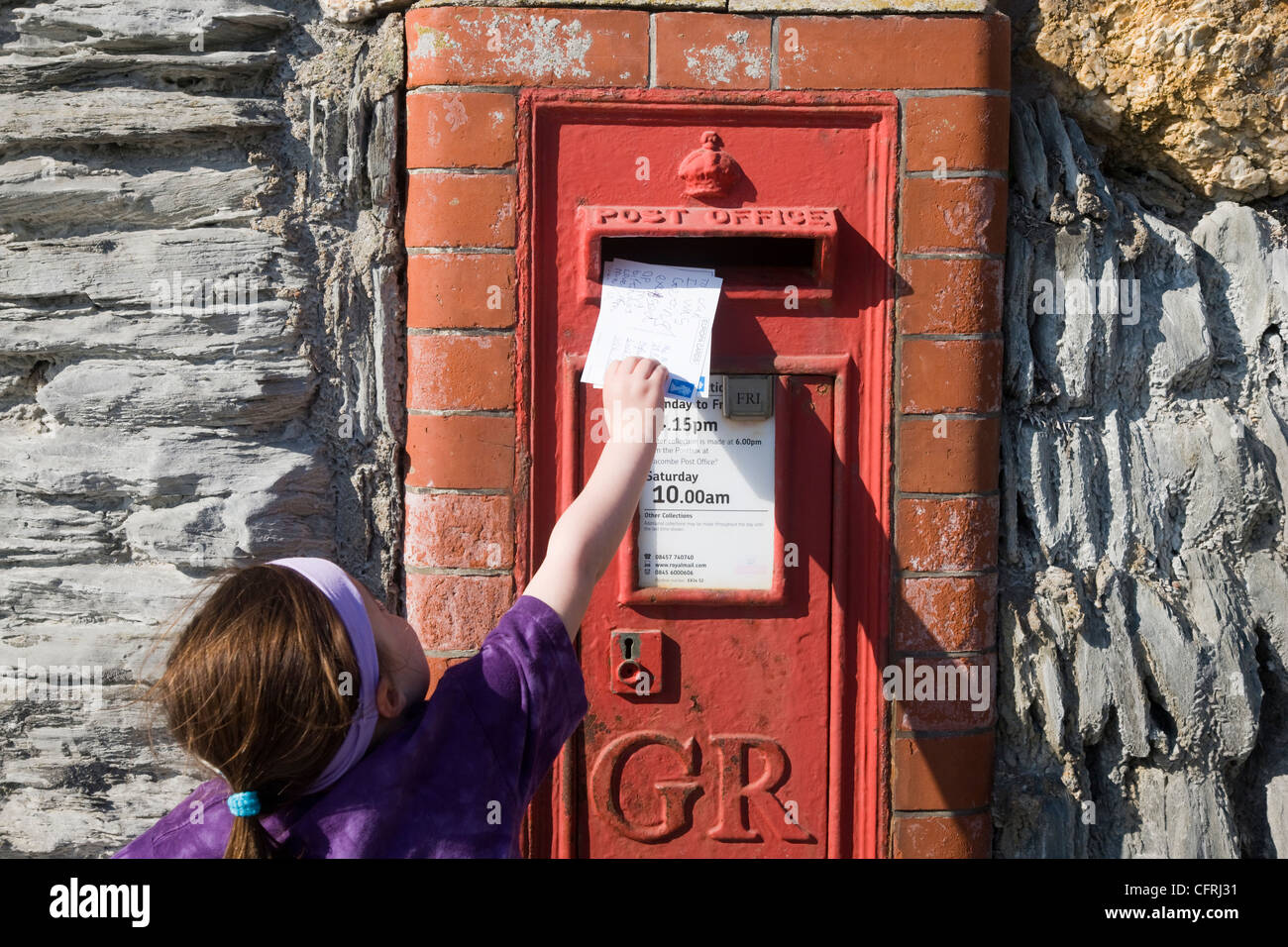 Little girl posting postcards into a red postbox in Woolacombe, Devon Stock Photo