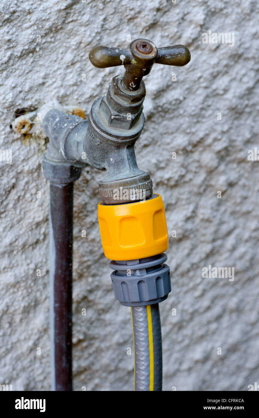 Outdoor garden water tap with hose pipe connected. - Stock Image