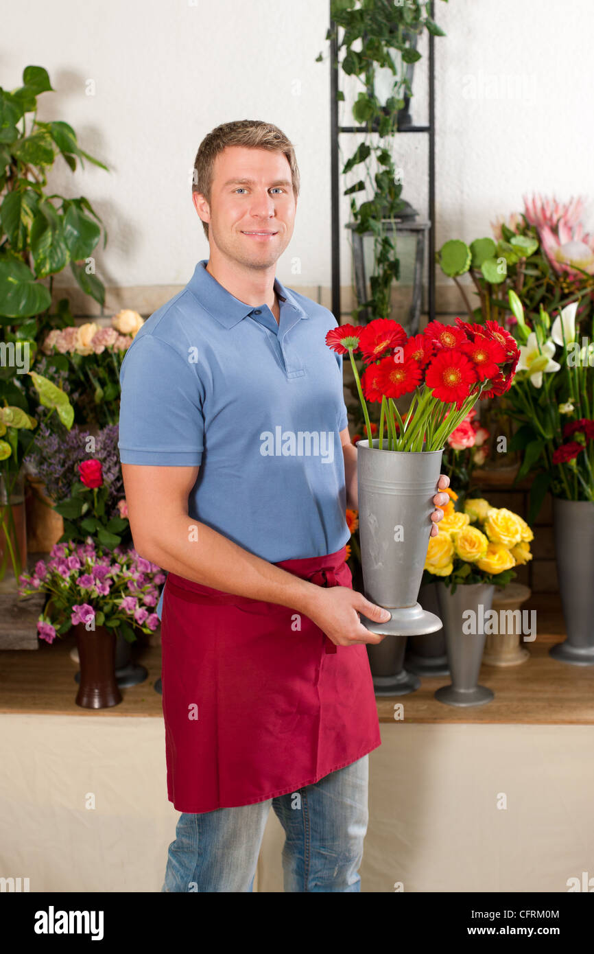 Male Florist in flower shop or nursery presenting his plants on display Stock Photo