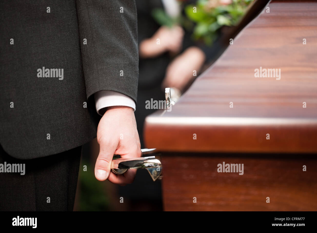 Religion, death and dolor - coffin bearer carrying casket at funeral to cemetery - Stock Image