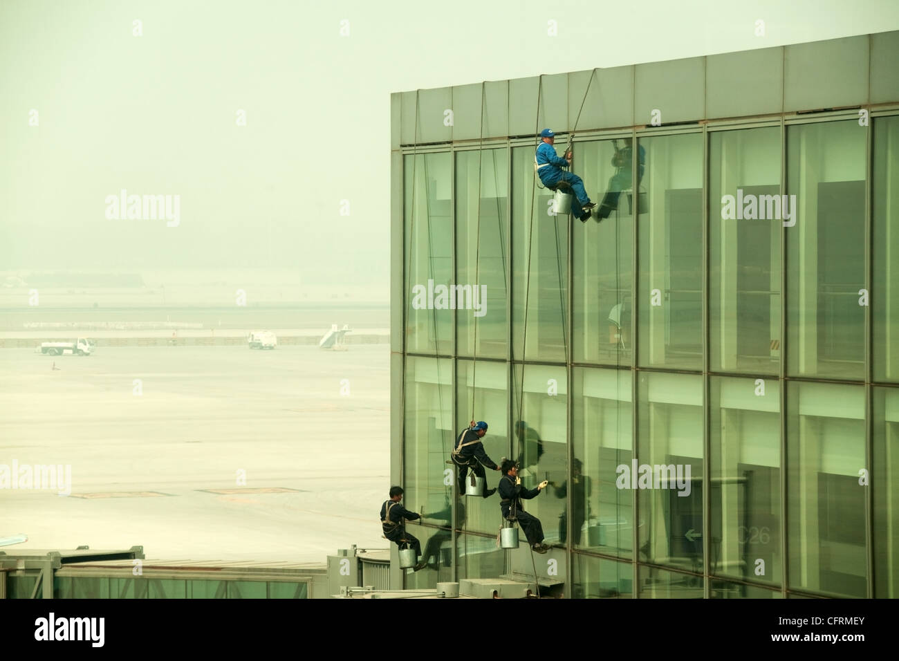 Hanging windows cleaners at Beijing Airport, China - Stock Image
