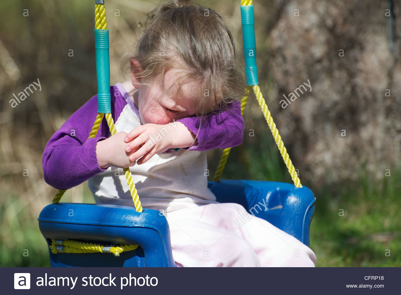 Close up image of a toddler crying on her swing in the summer. - Stock Image