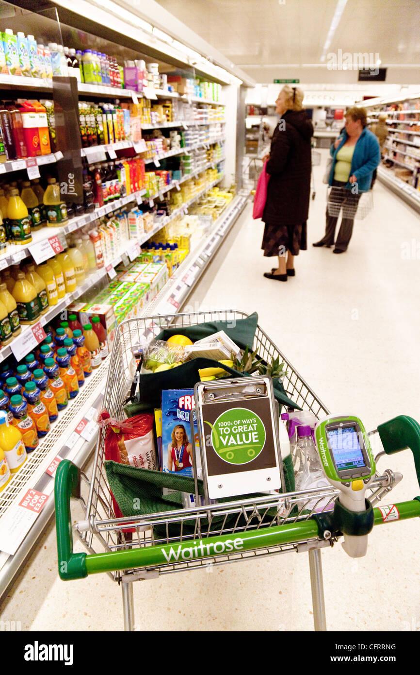 A full supermarket trolley in an aisle in Waitrose, Newmarket Suffolk UK - Stock Image