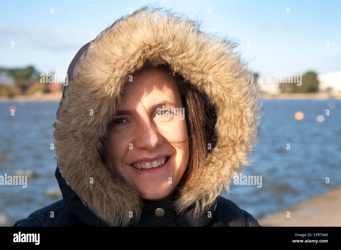 Young woman with fur trimmed hooded coat on the South West Coast of England, UK - Stock Image