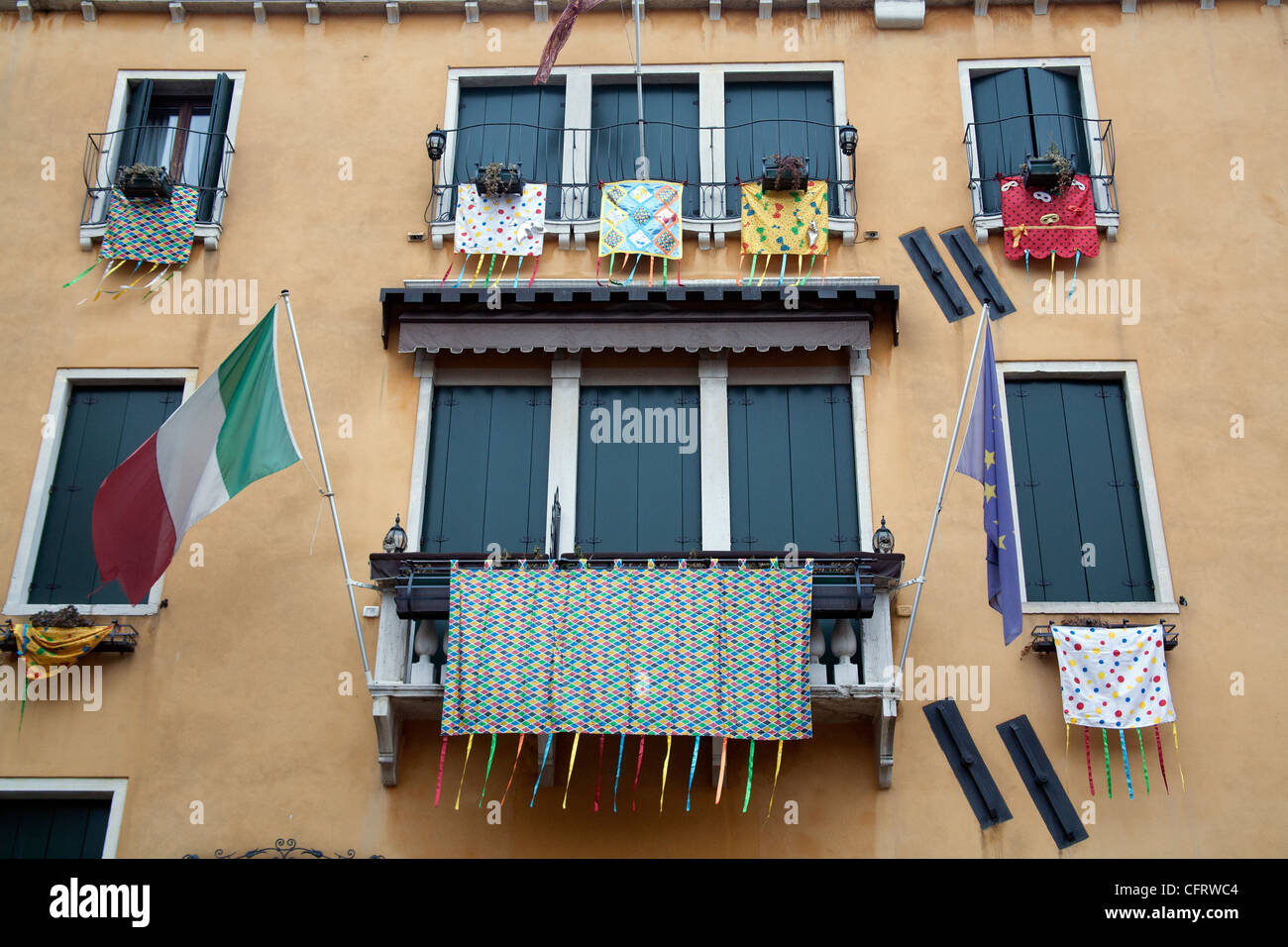 Carnival decorations hanging from the windows of the Hotel Ala, Venice Italy - Stock Image