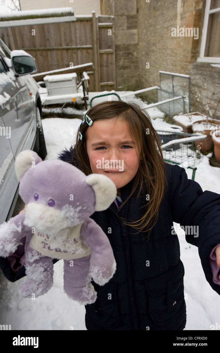 Little girl crying and upset because she dropped her best cuddly toy teddy in the snow - Stock Image