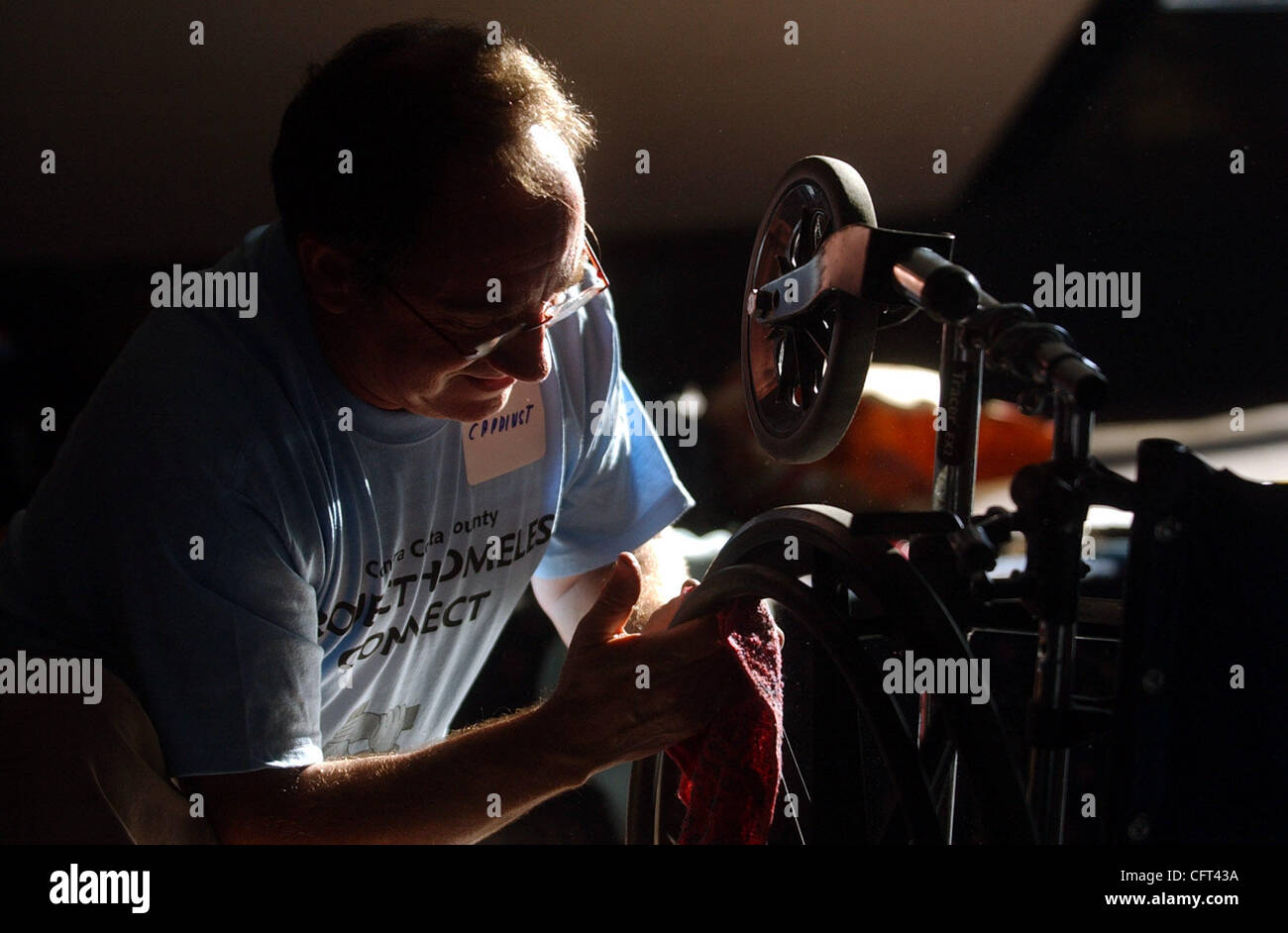 Paul Cardinet, a public health nurse, knows bikes but is doing repair work on wheelchairs to help Project Homeless - Stock Image