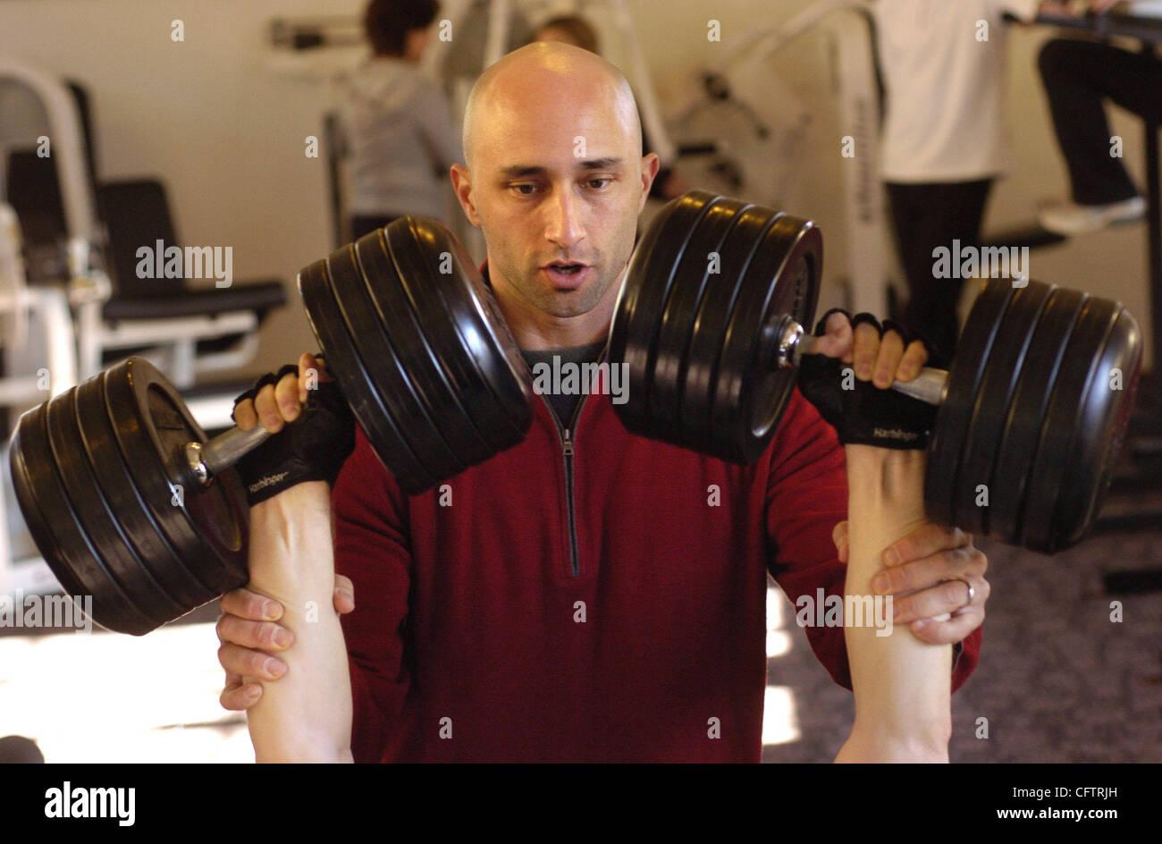 Personal trainer Brian Rivera helps his client, Dan Martin