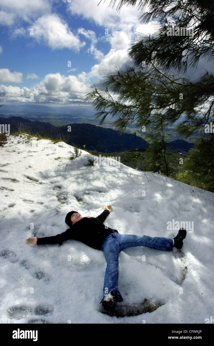 Ryley Shepherd, 7, of Antioch makes a snow angel on a closed-to-cars portion of Summit Road halfway up to the peak - Stock Image