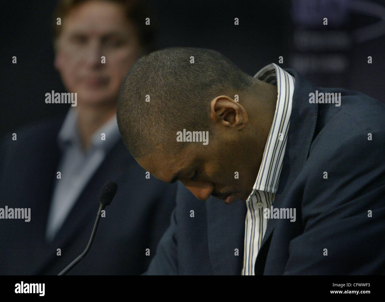 As Kings President Geoff Petrie in the background looks on, Kings player Ron Artest takes a short break and gets - Stock Image