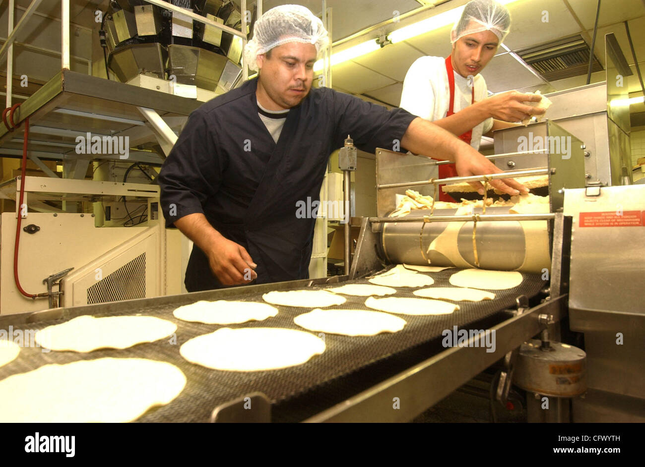 Mar 14, 2007 - Millbrae, CA, USA - JUAN VAZQUEZ, left, and Juan Carlos operate machinery that cuts tortillas at - Stock Image