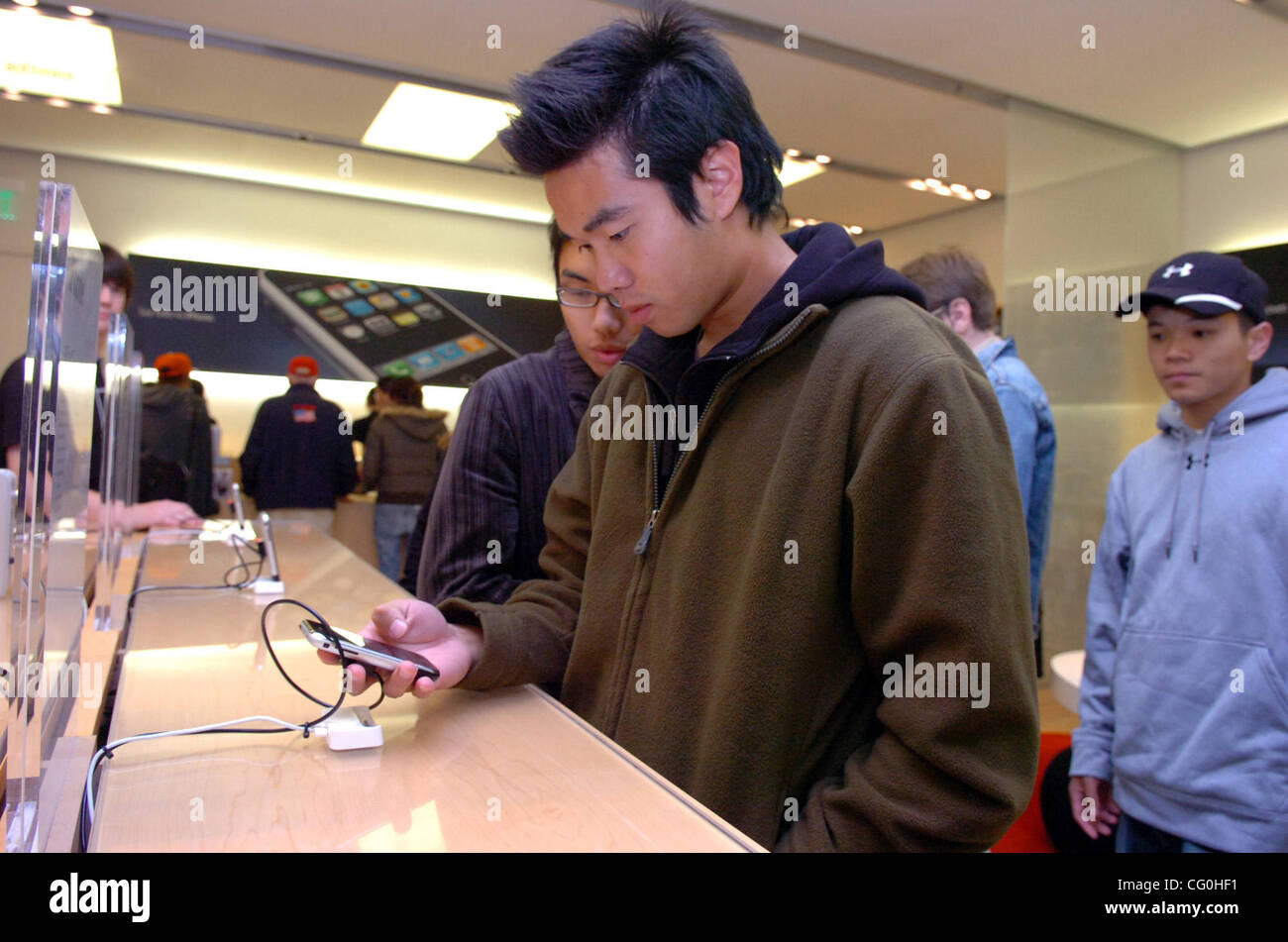 Alan Fung of San Diego tries out an iPhone before making his purchase at the Apple Store in Emeryville on Friday - Stock Image