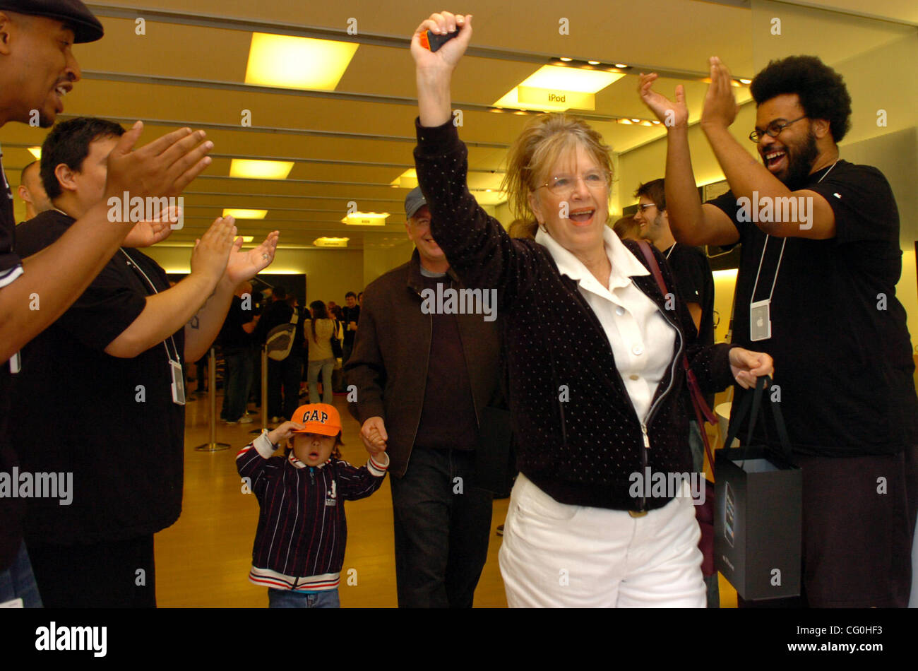 Barbara Allendorf of Berkeley celebrates after buying an iPhone at the Apple Store in Emeryville on Friday June - Stock Image