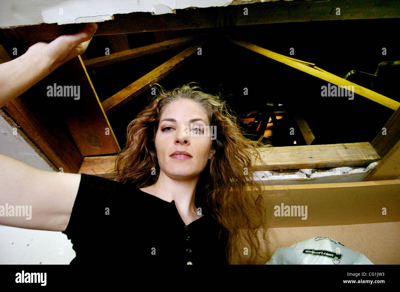 Michaela Brewer stands at the entrance to the attic of her Tracy home on Saturday, August 18, 2007. Mrs. Brewer - Stock Image