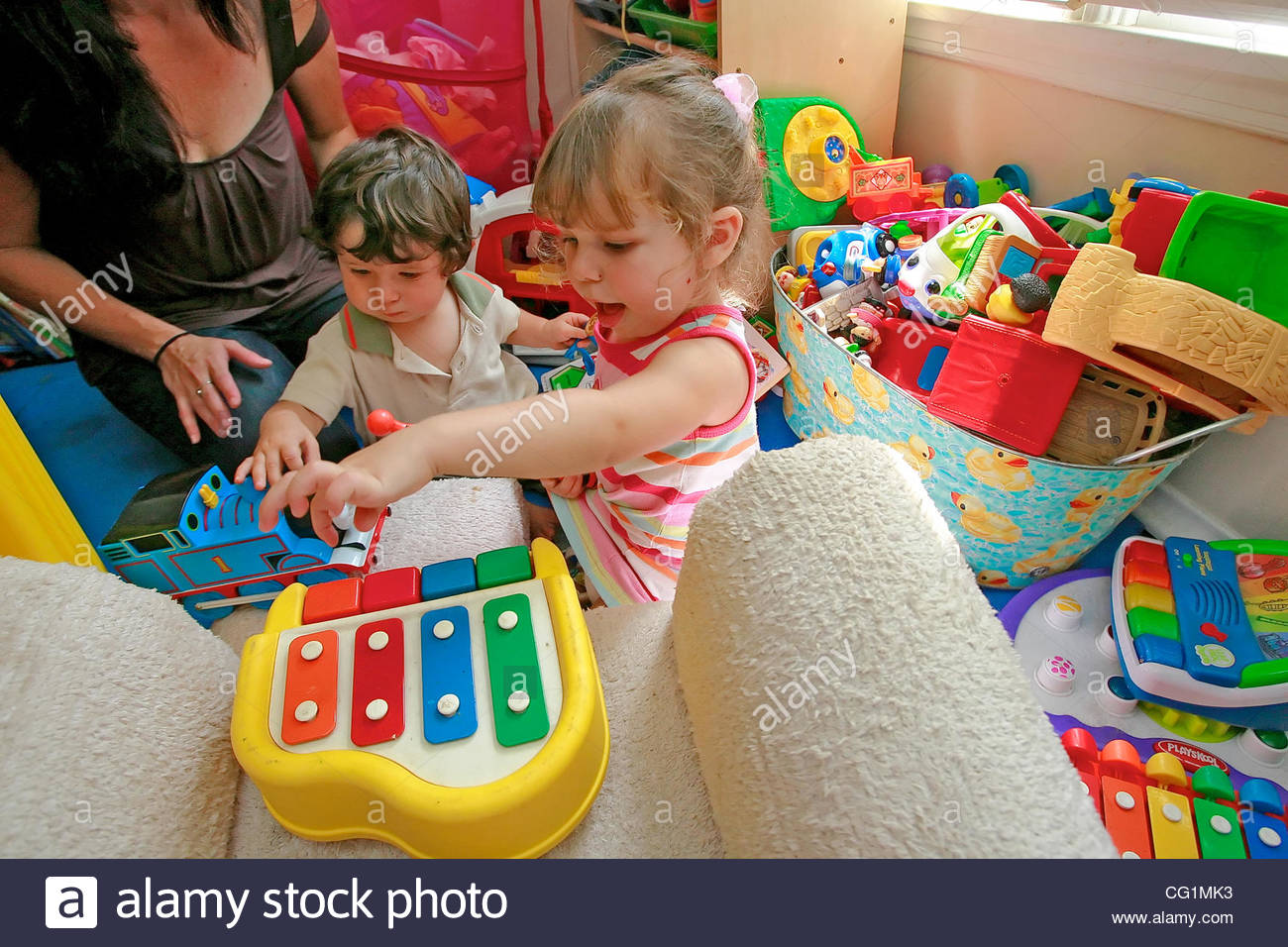 Dana Laine Parker of Westchester, CA, watches her 13-month-old son Toby and 2 1/2-year-0ld Ivy play with their toys - Stock Image