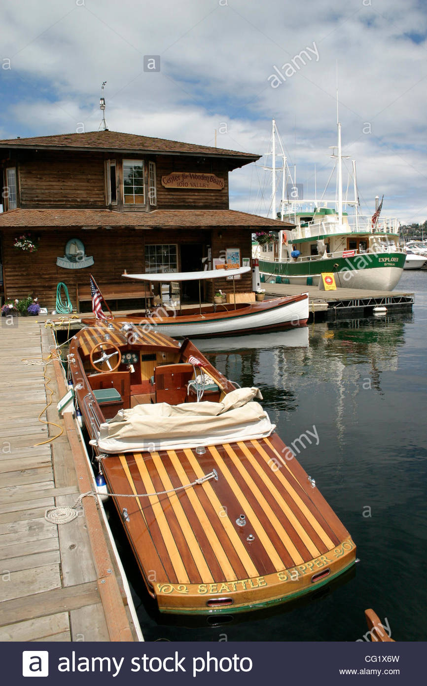 some classic water craft are tied up at the center for wooden boats