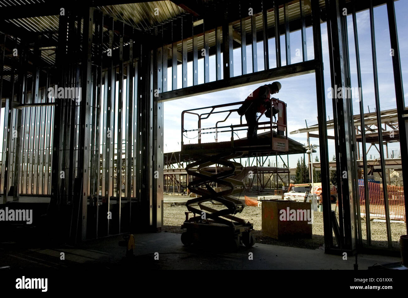 LEDE-- Metal stud framing is installed by a construction worker who ...