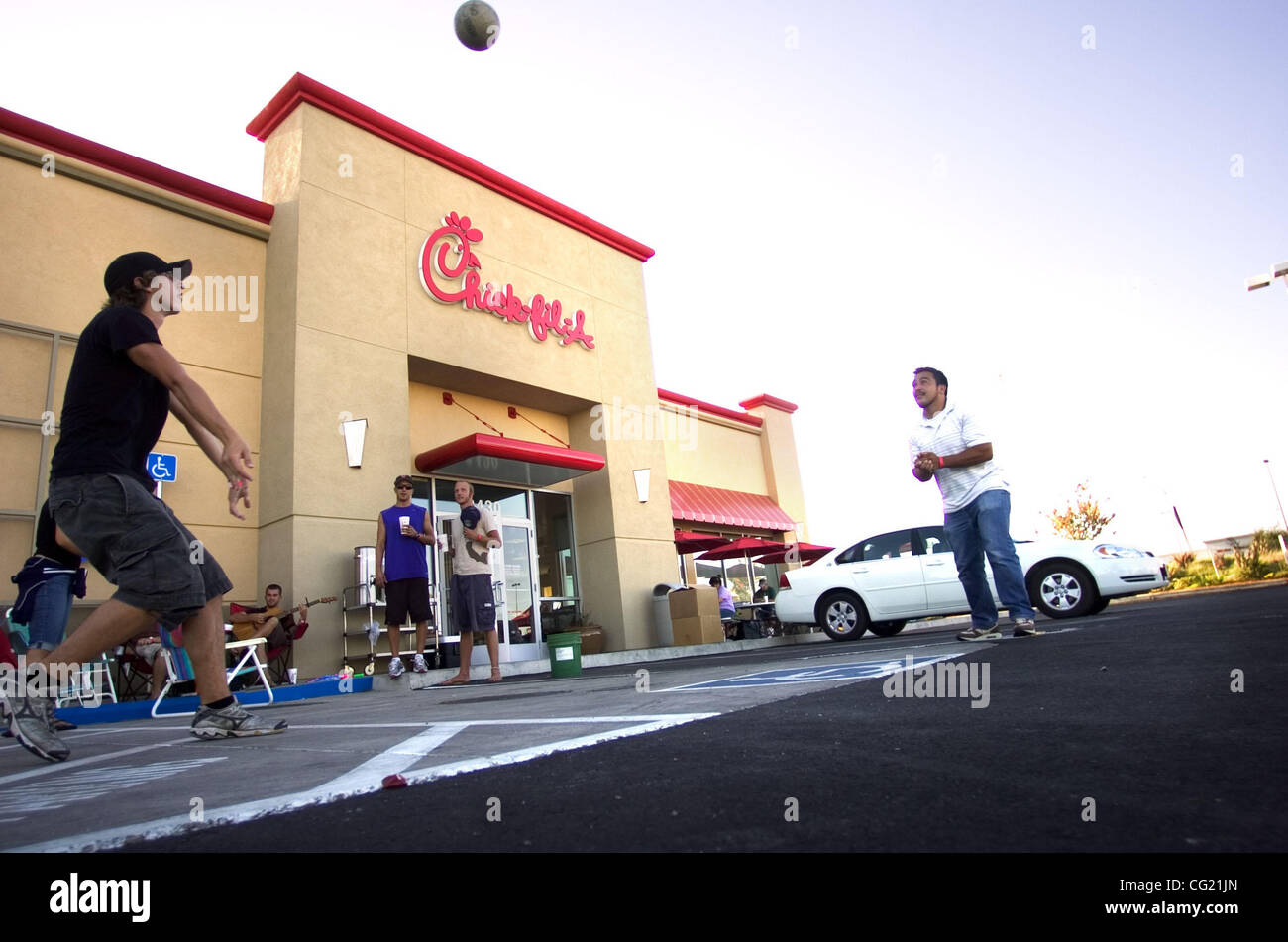 LEDE: Future Chic-Fil-A customers Josh Moog, left, and Jose Perez pass time with volleyball in the parking lot of - Stock Image