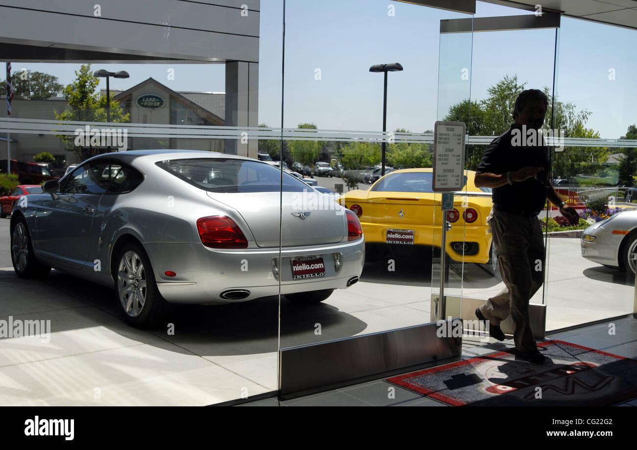 A Bentley and a Ferrari are displa at Niello Porsche, which is ...