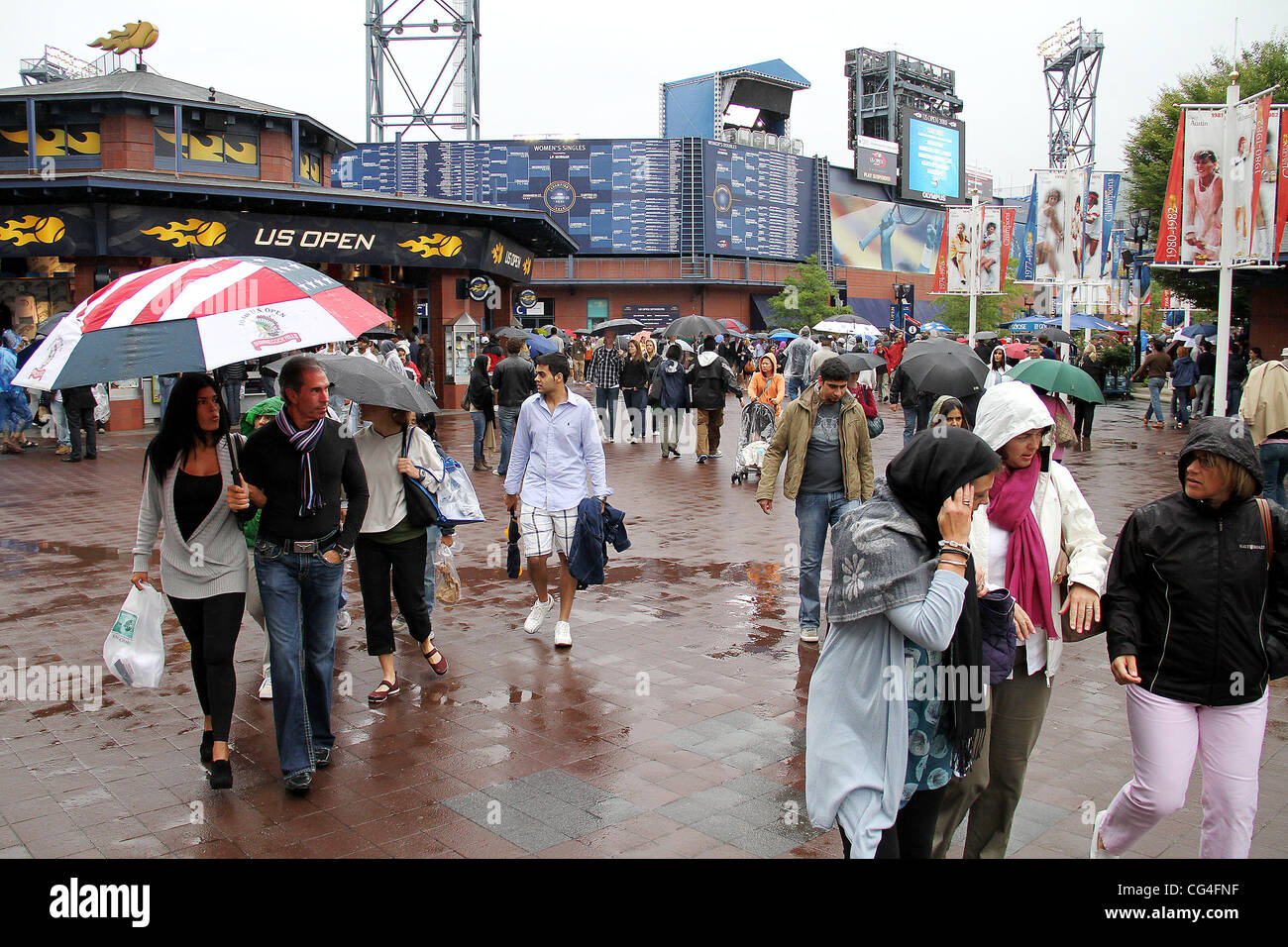 Fans brave the rain at the USTA Arthur Ashe Stadium in Flushing, Queens. The US Open men's tennis final championship - Stock Image