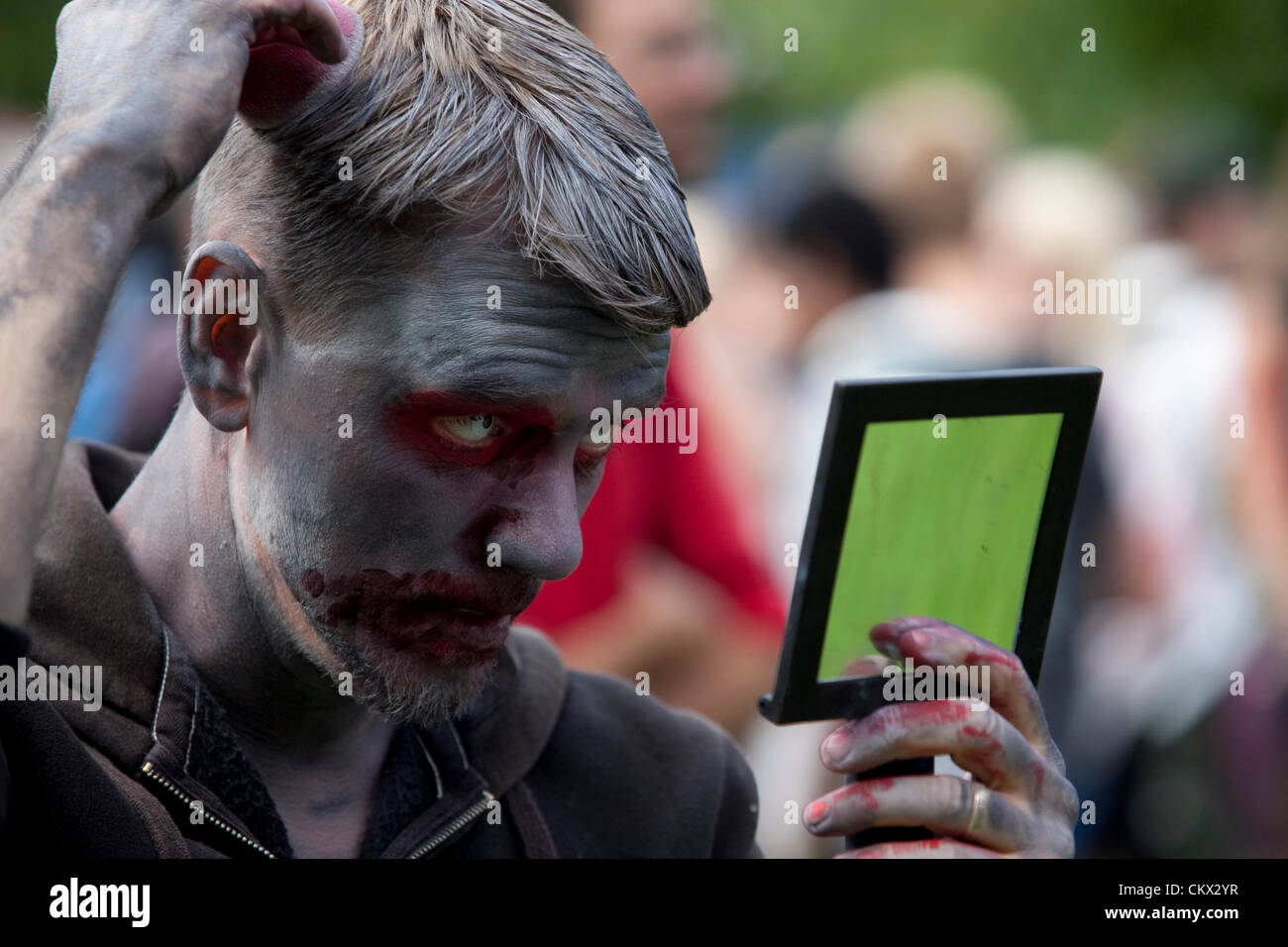 A Zombie at Stockholm Zombie Walk 2012. A guy putting the finishing touches on his zombie makeup. - Stock Image