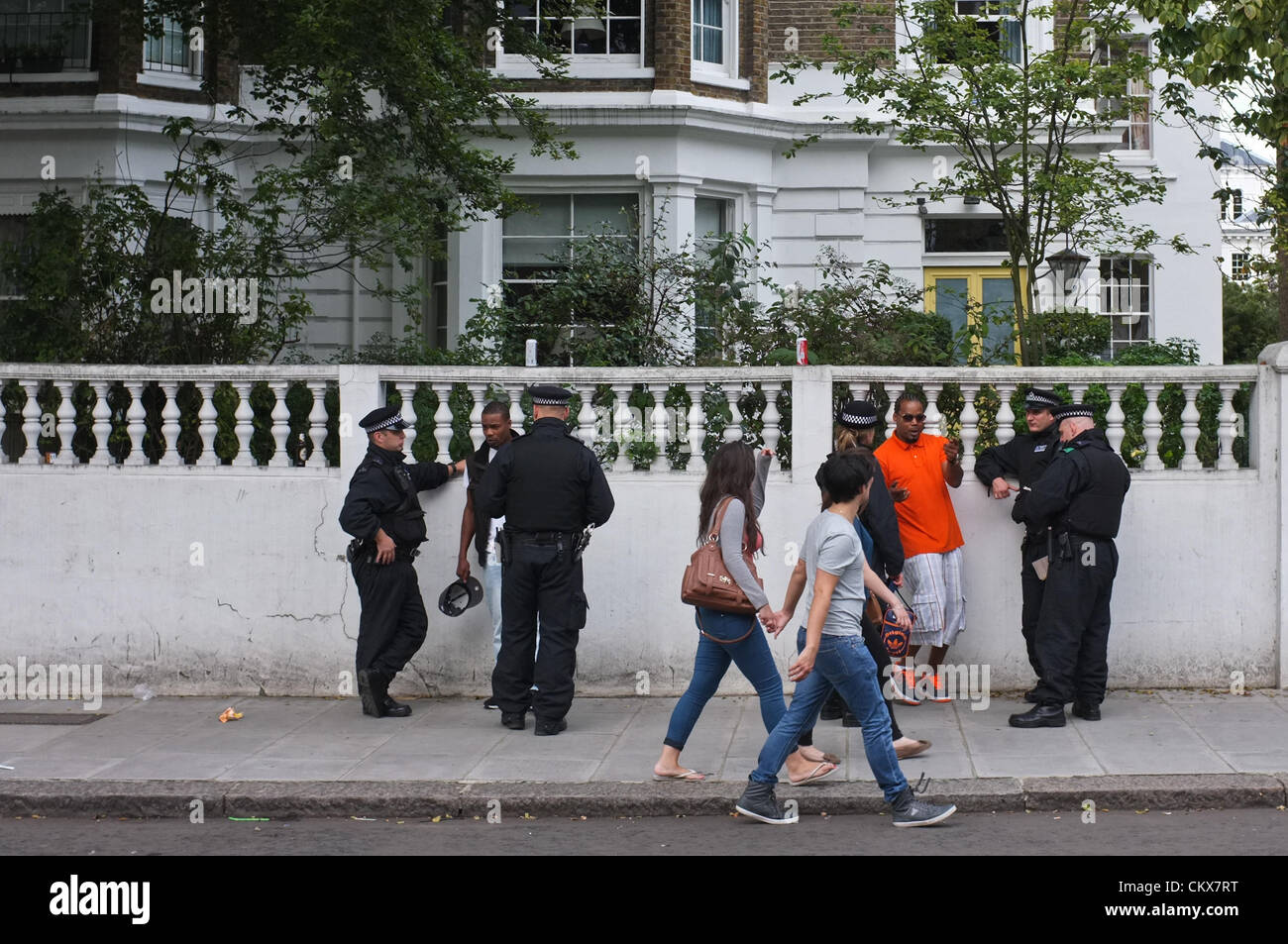 26th Aug 2012. London, UK.Police questioning men at the Notting HIll Carnival in August 2012 - Stock Image