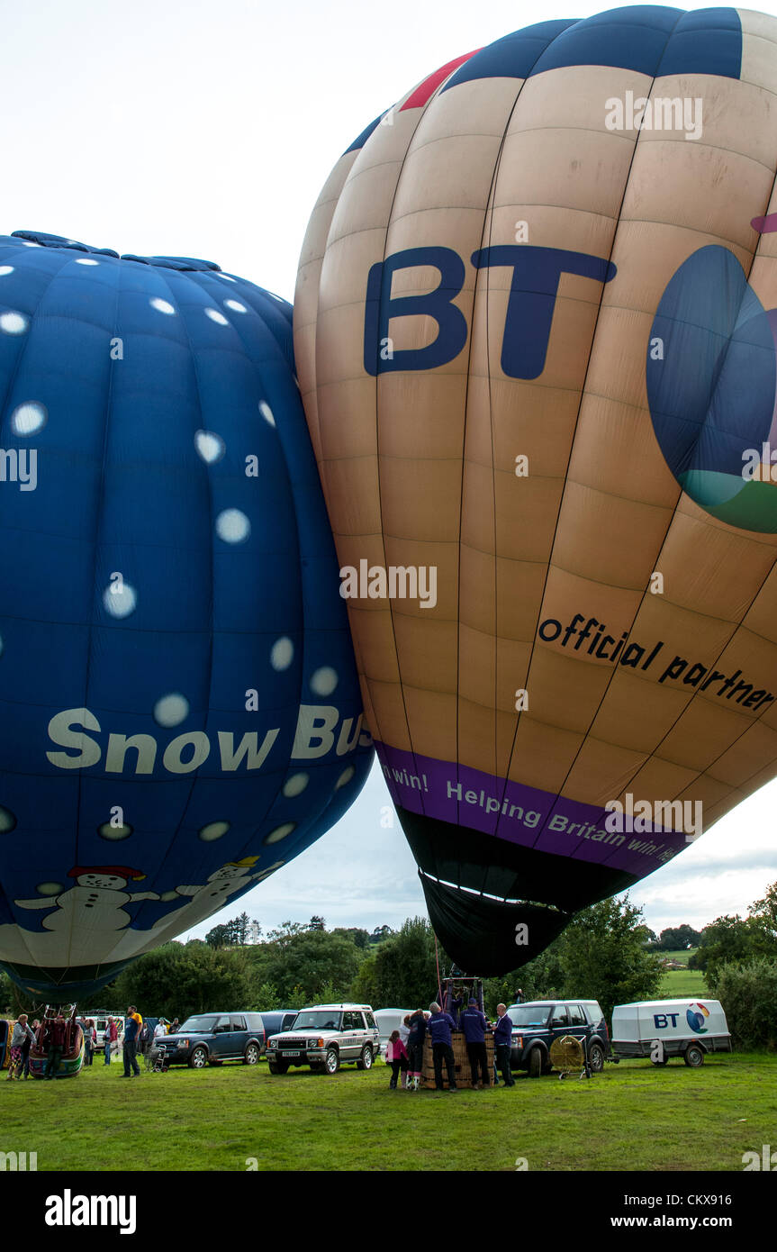 26th Aug 2012. Dave Baker G-ZOIZ M-Type (M-105) BT LONDON 2012 balloon and the G-SBIZ Cameron Z.90 Snow Business Hot Air Free Balloon bump together as they prepare for launch at the Tiverton balloon festival in Tiverton, Devon, UK. Stock Photo