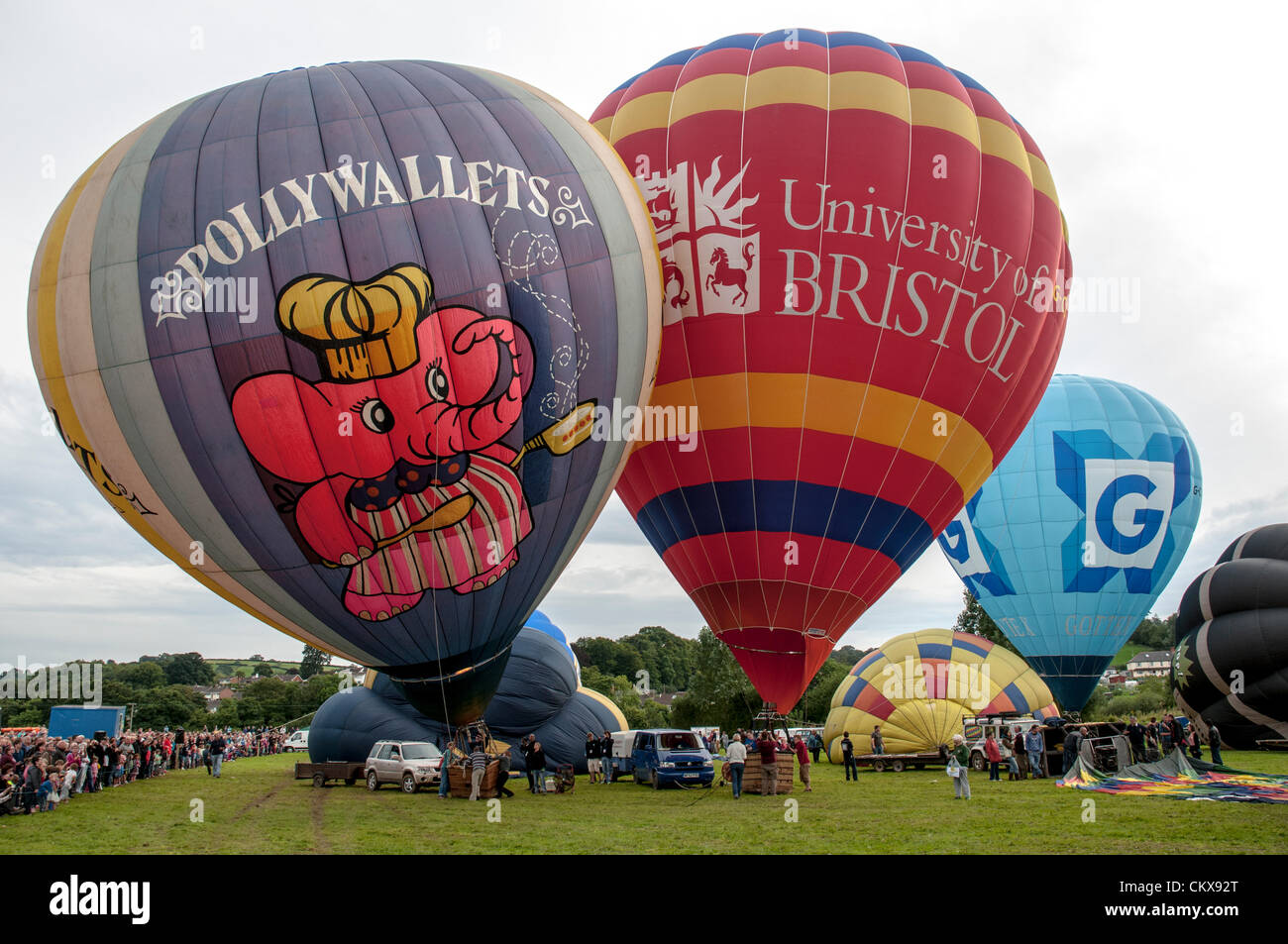 26th Aug 2012. The G-POLY, 1978 CAMERON N-77 Pollywallets ballon Cameron-Z Series (UK) (Gottex) (Z-90) (G-CCNN) balloon and the John Harris (G-CDWD)  University of Bristol balloon is prepared for launch at the Tiverton balloon festival in Tiverton, Devon, UK. Stock Photo