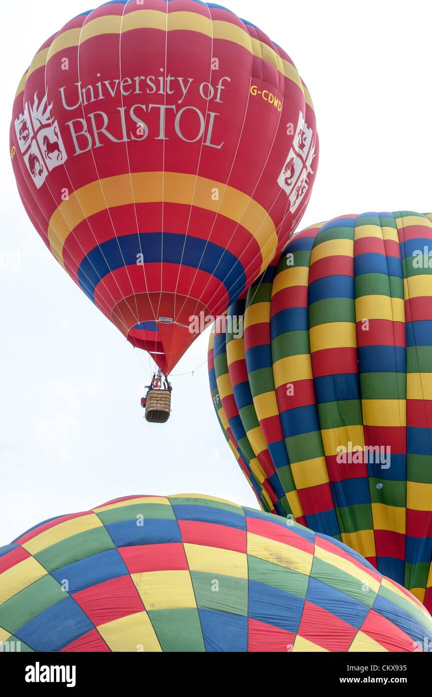 26th Aug 2012. The John Harris (G-CDWD) University of Bristol balloon takes off beside the Colin Hodges G-CFFL Lindstrand LBL-317A Aerosaurus balloon at the Tiverton balloon festival in Tiverton, Devon, UK. Stock Photo