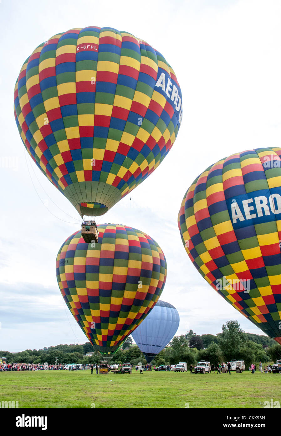 26th Aug 2012. The the Colin Hodges G-CFFL Lindstrand LBL-317A Aerosaurus balloon takes off between the G-CCRS - Lindstrand Aerosaurus balloon and the G-CDHN Lindstrand LBL-317A Aerosaurus balloon at the Tiverton balloon festival in Tiverton, Devon, UK. Stock Photo