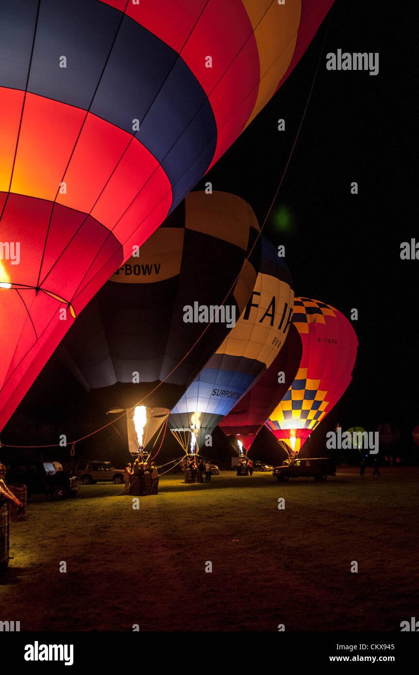 26th Aug 2012. The John Harris (G-CDWD) University of Bristol balloon,the Robert Harris G-BOWV Cameron V-65 balloon, the Peter harding LINDSTRAND 90A Fairway Furniture balloon, the CAMERON V-56 G-BFFT balloon and the Charlie Street Lindstrand LBL-105A, G-CGXO, Aerosaurus Balloon light-up during the nightglow at the Tiverton Balloon festival, Devon, UK. Stock Photo