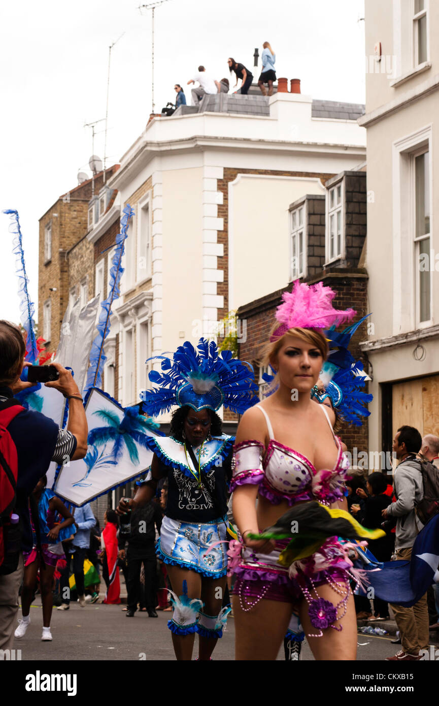 London, UK - 27 August 2012: a party-goer takes part at the parade during the Notting Hill Carnival while people - Stock Image