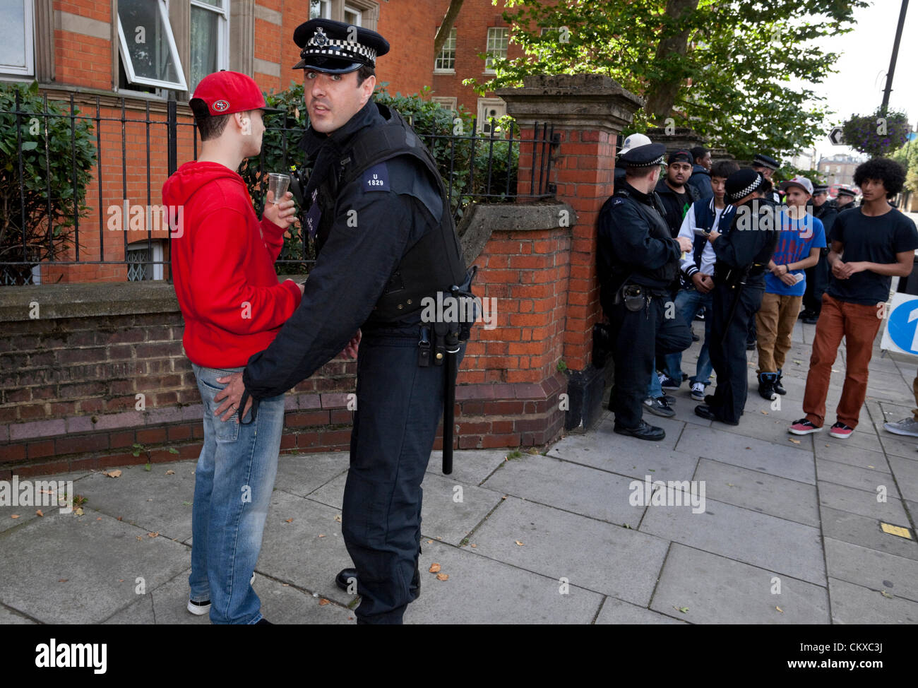 August 27th, 2012, London, UK. A group of Metropolitan police officers stop and search a group of youths at the - Stock Image