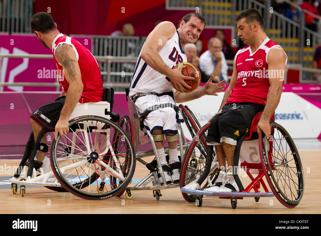 USA's Joshua Turek squeezes between two Turkish during wheelchair basketball game at the 2012 London Paralympics. - Stock Image