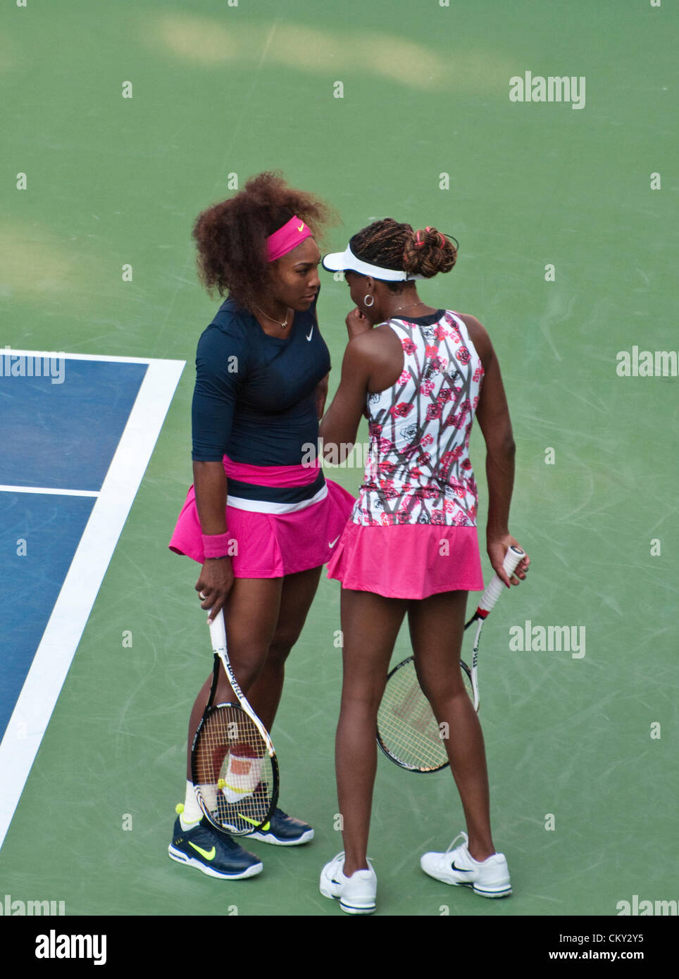 Serena Williams and Venus Williams of the USA discuss strategy during the women's doubles second round match - Stock Image