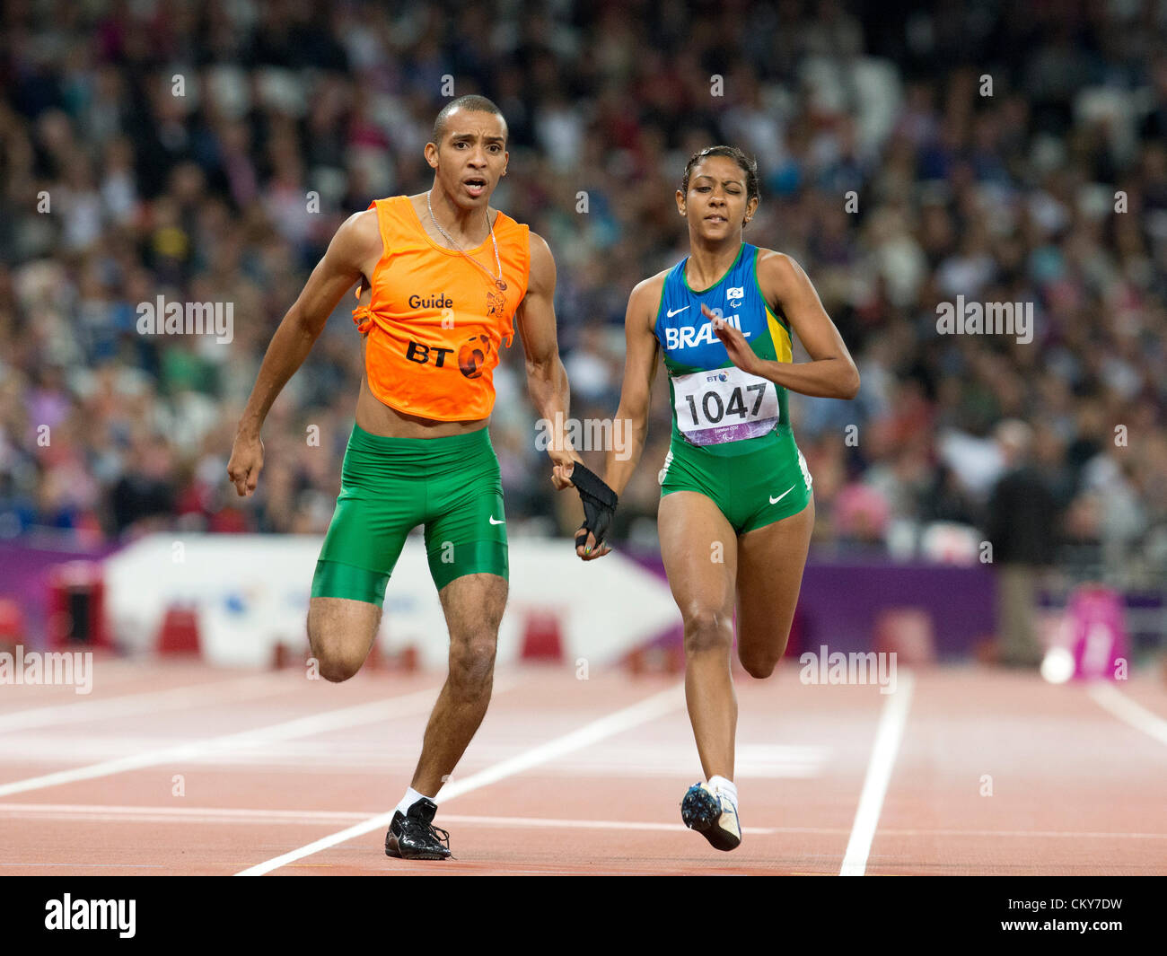Alice de Olivera Correa of Brazil with her guide Diogo da Silva runs in the women's 100 m T12 at the 2012 London - Stock Image