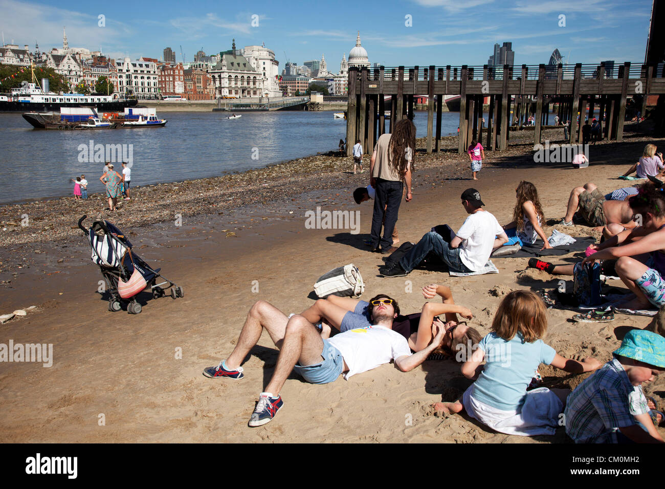 London, UK. 8th September, 2012. People gather on the sand beach shore of the river Thames, like the seaside in - Stock Image