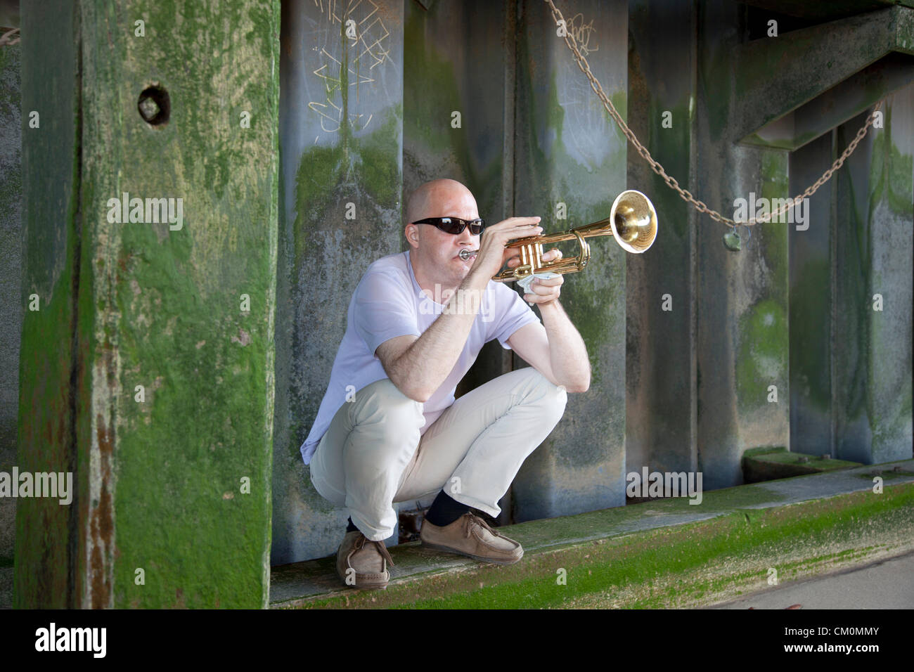 London, UK. 8th September, 2012. Man plays a trumpet underneath Blackfriars Bridge on the shore of the river Thames. - Stock Image