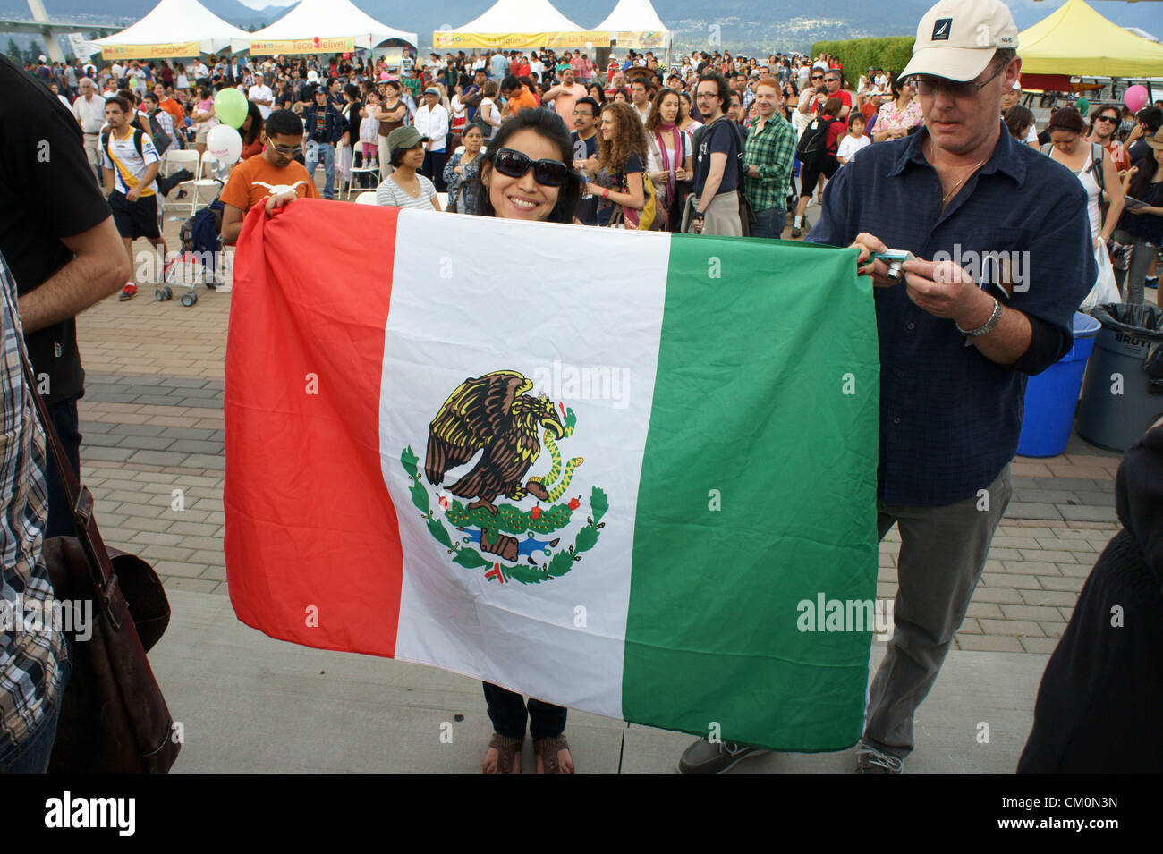 Woman holding up a Mexican flag at the Mexico Fest Mexican independence day celebrations in Vancouver, British Columbia, - Stock Image