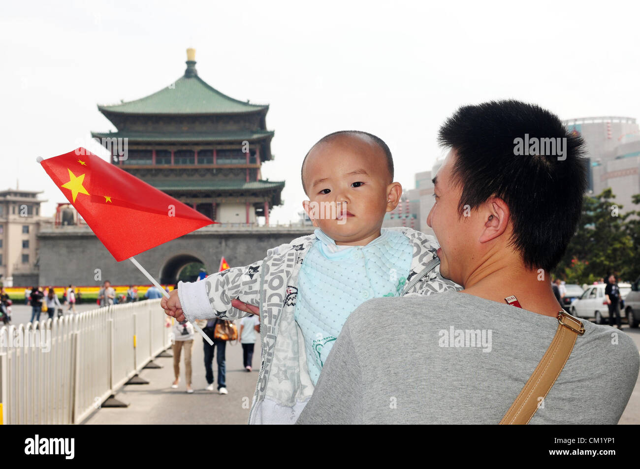 Xian, China. Saturday 15th September, 2012. A young father with his little son holding a Chinese national flag walks Stock Photo