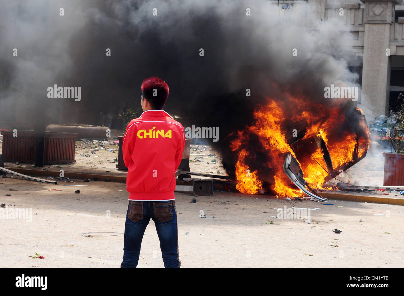 Xian, China. Saturday 15th September, 2012. Anti-Japanese protesters burn a car during a demonstration at Bell Tower Stock Photo