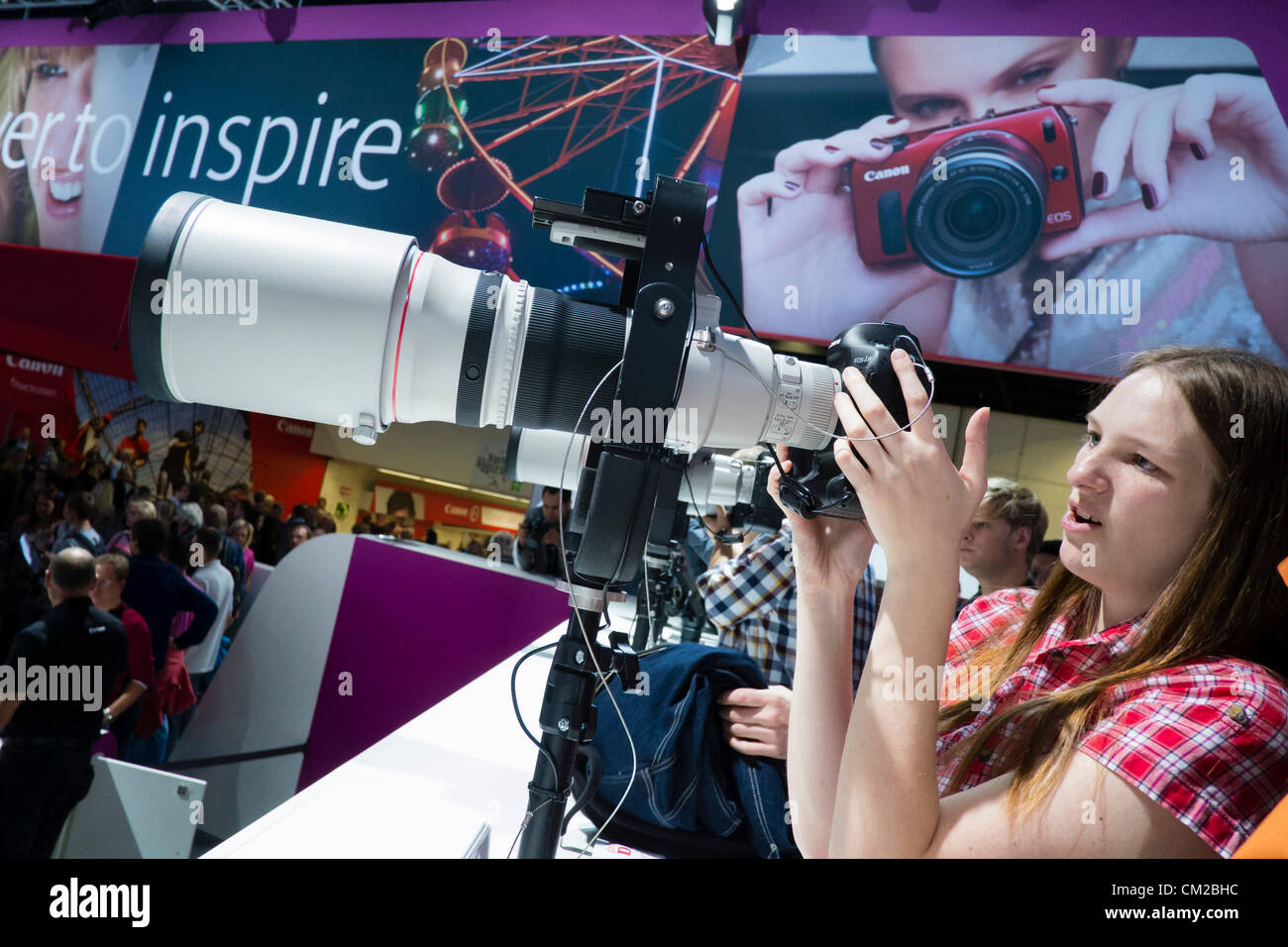 Visitors to the Canon stand try out a selection of large telephoto lenses on the second day of bi-annual Photokina - Stock Image