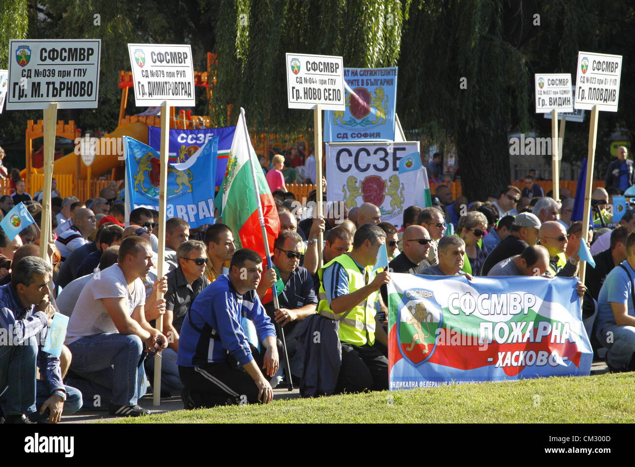 Demonstrators kneeling at the beginning of the rally to keep the customary minute of silence. The signs show the - Stock Image
