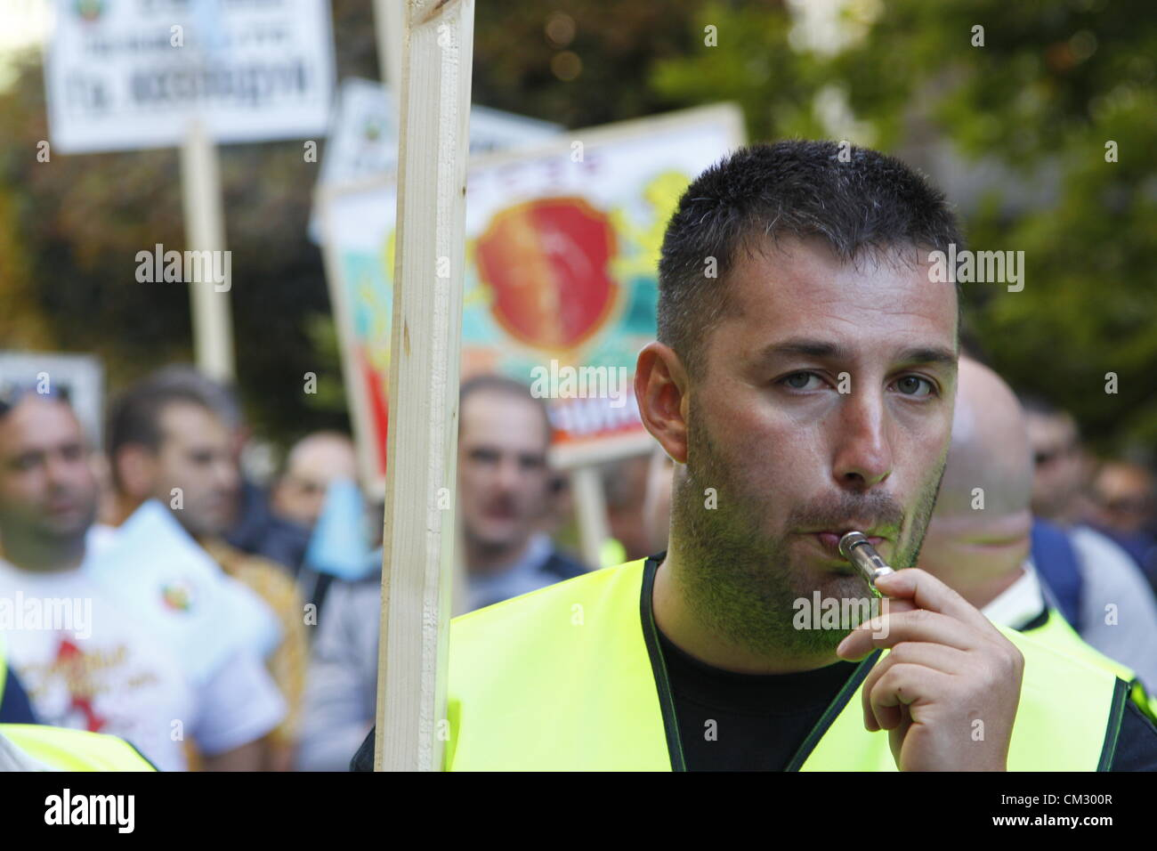 Demonstrator holding a sign, blowing his whistle in front of the Bulgarian Finance Ministry in protest of the low - Stock Image