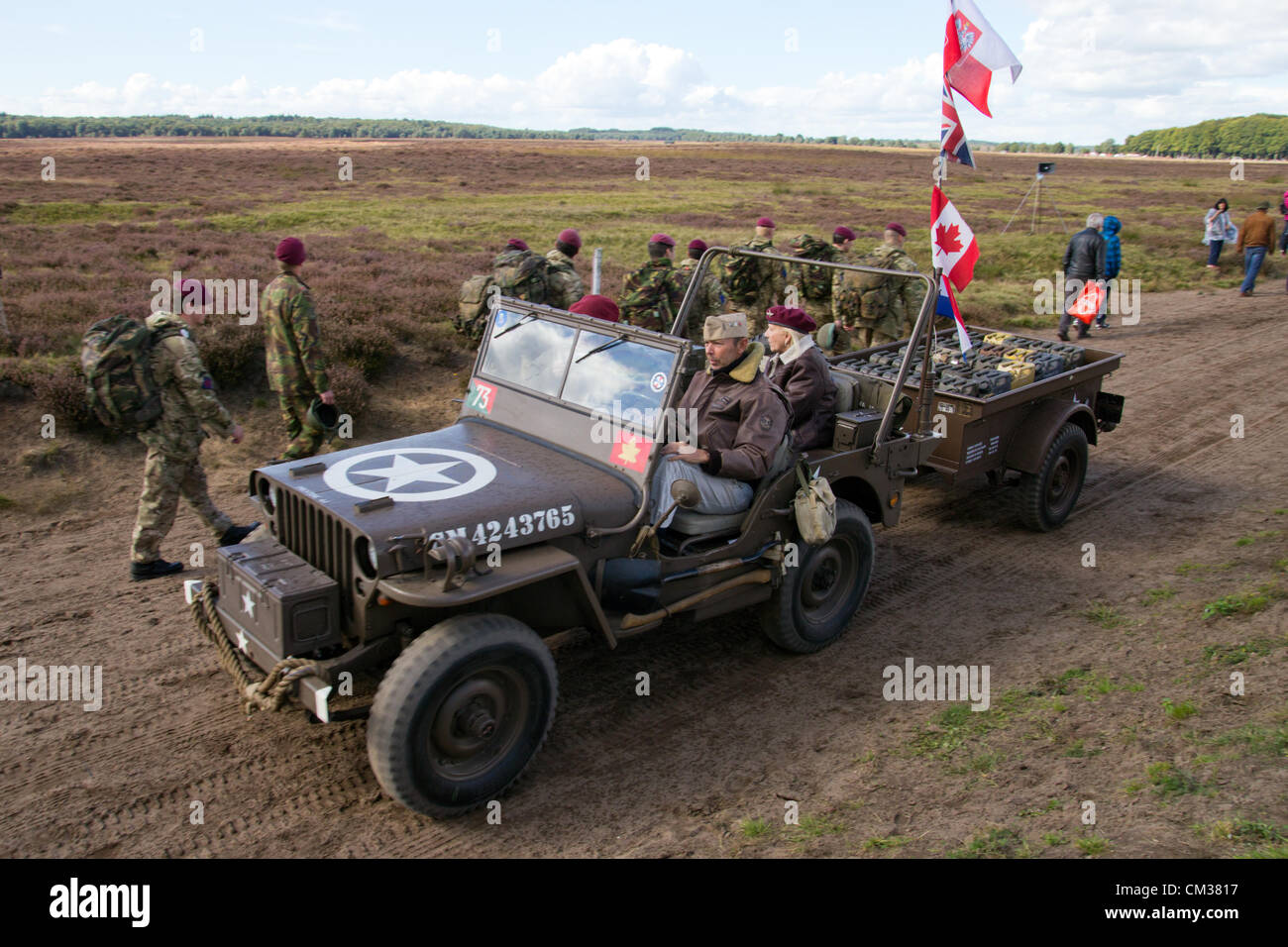 A WW2 Jeep drives past British paratroopers during the Market Garden Memorial, Ginkelse Heide, The Netherlands, - Stock Image